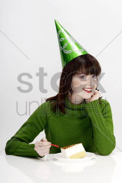 woman with party hat eating cake stock photo