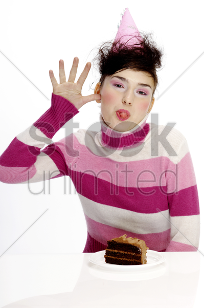 woman with party hat sticking out her tongue stock photo