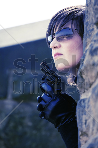 woman with pistol hiding behind a tree stock photo