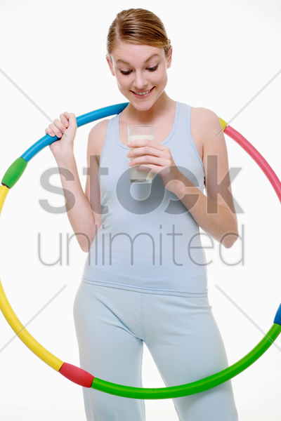 woman with plastic hoop looking into glass of milk stock photo
