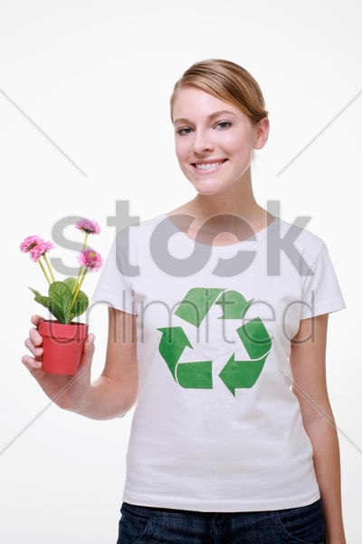 woman with recycling symbol on her t-shirt holding a potted plant stock photo