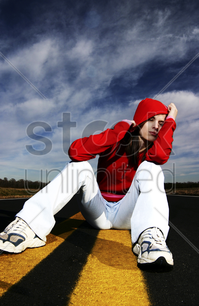 woman with red hooded jacket sitting in the middle of the road stock photo