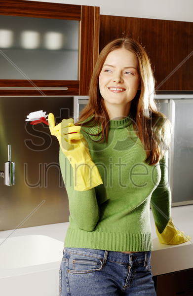woman with rubber gloves holding a brush stock photo