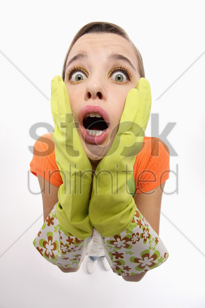 woman with rubber gloves looking shocked stock photo
