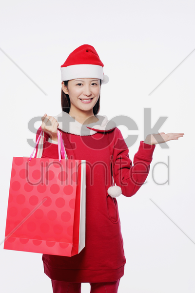 woman with santa hat carrying shopping bags stock photo