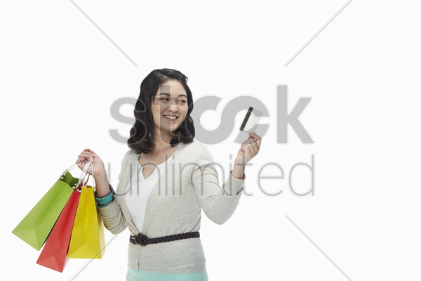 woman with shopping bags holding up a credit card stock photo