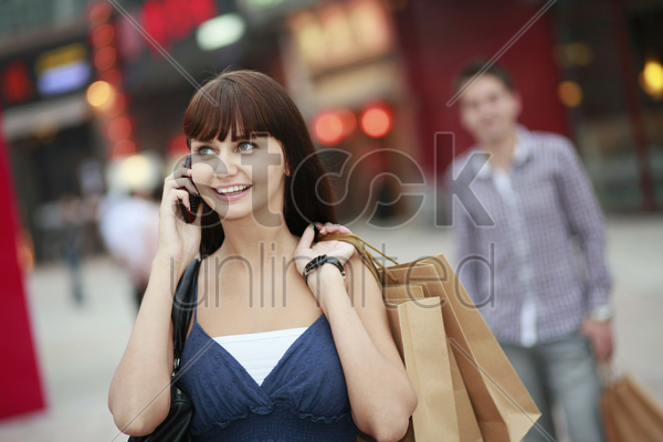 woman with shopping bags talking on the phone stock photo