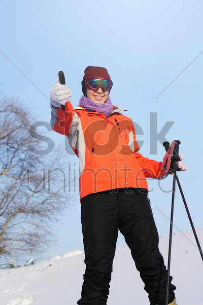 woman with skis and poles showing thumbs up stock photo