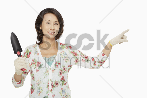 woman with spade showing hand gesture stock photo