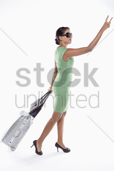 woman with suitcase pointing above stock photo