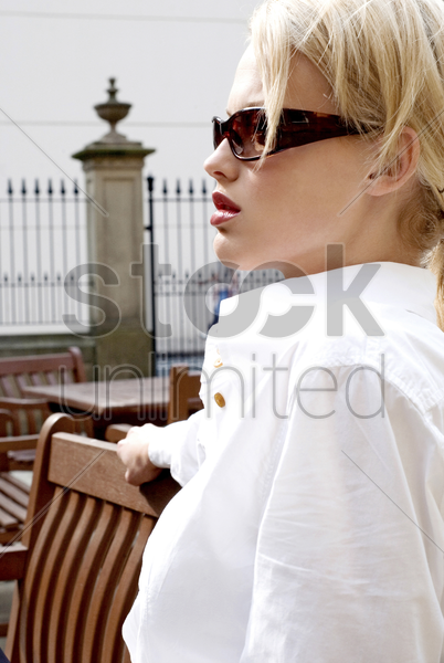 woman with sunglasses sitting on the bench stock photo