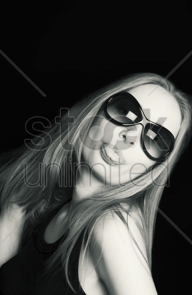 woman with sunglasses sticking out her tongue stock photo