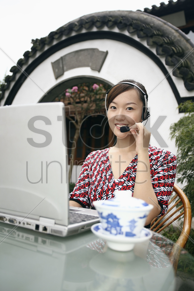 woman with telephone headset using laptop stock photo
