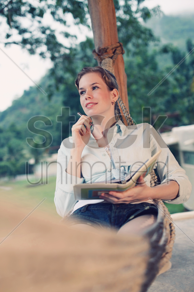 woman writing diary in hammock stock photo