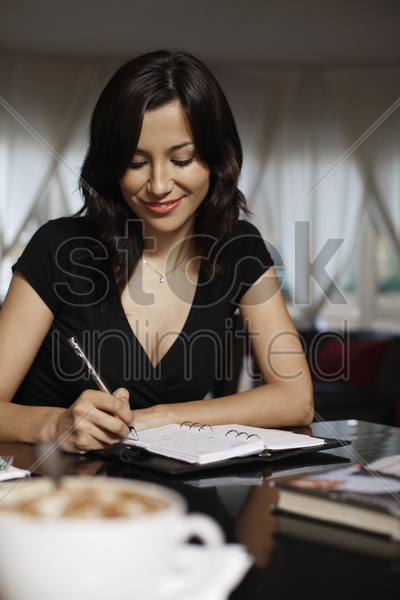 woman writing in an organizer stock photo