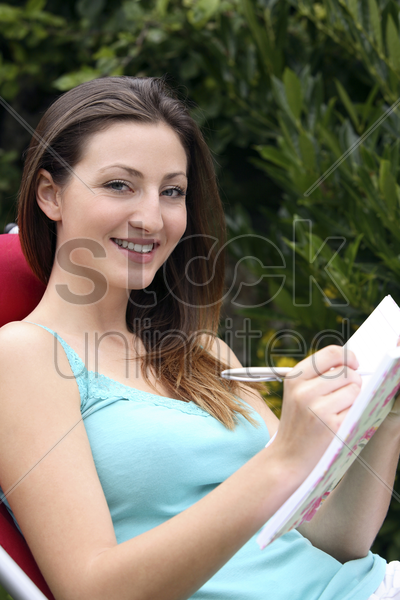 woman writing in her diary stock photo