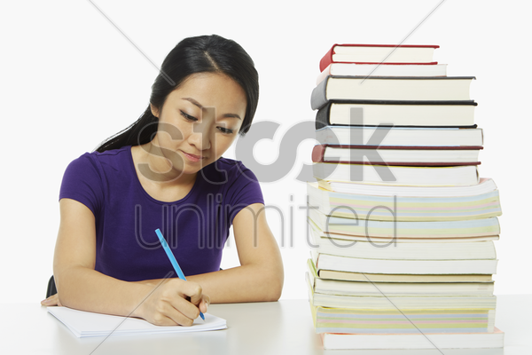 woman writing notes in book stock photo