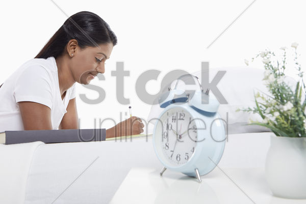 woman writing notes while laying on bed stock photo