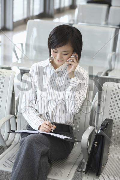 woman writing on organizer while taking on the phone stock photo