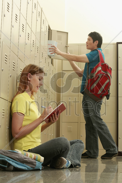 woman writing some notes while man is keeping his books in the locker stock photo