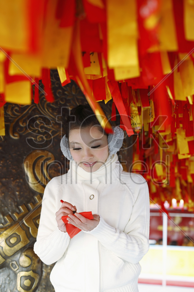 woman writing wishes on red ribbon stock photo