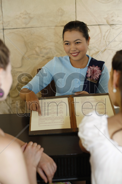 women being showed choices of spa available at resort stock photo