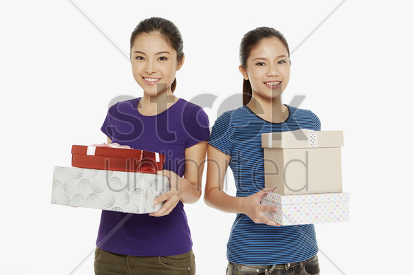women carrying a stack of gift boxes stock photo