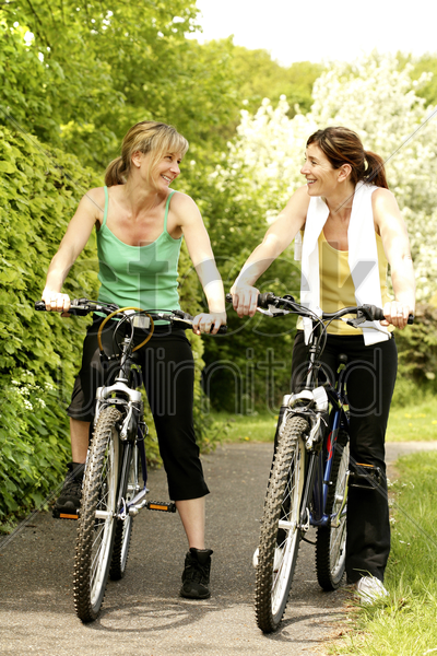 women chatting while sitting on bicycles stock photo