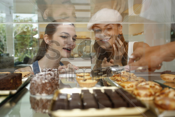 women choosing cakes and tarts from display case stock photo