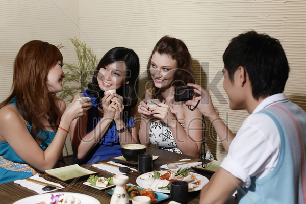 women drinking and chatting, man taking picture stock photo