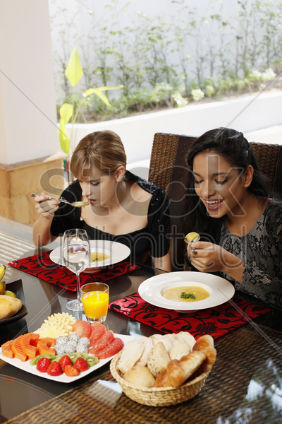 women enjoying pumpkin soup stock photo