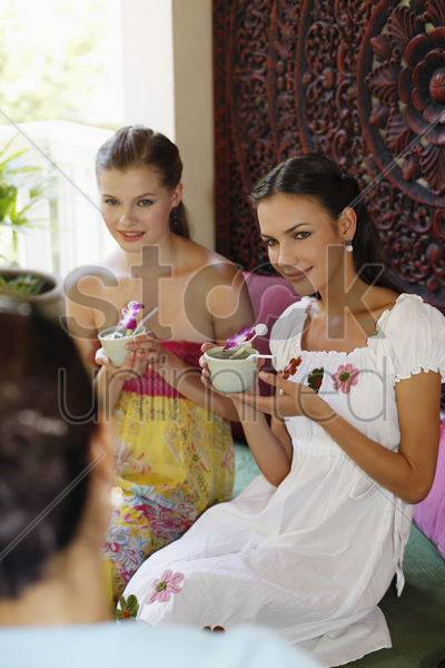 women enjoying tea while listening to customer service representative's explanation stock photo