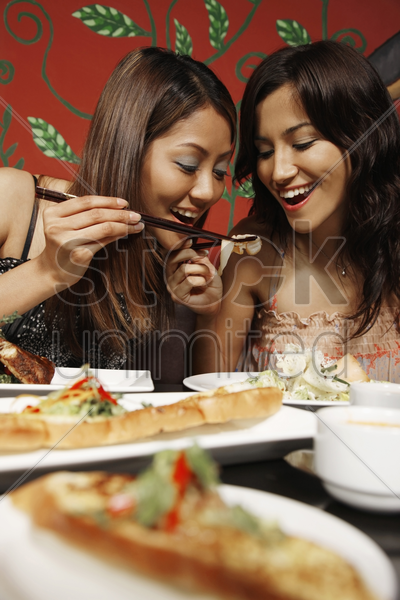 women fighting over salmon with chopsticks stock photo