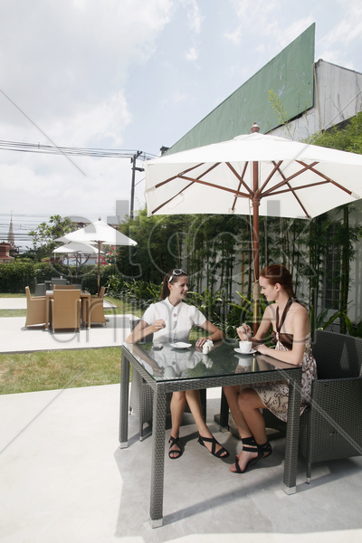 women having coffee together outdoors stock photo