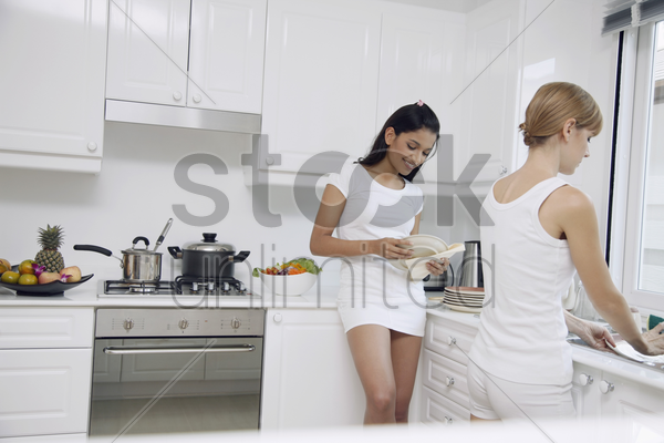 women having fun while washing dishes in the kitchen stock photo