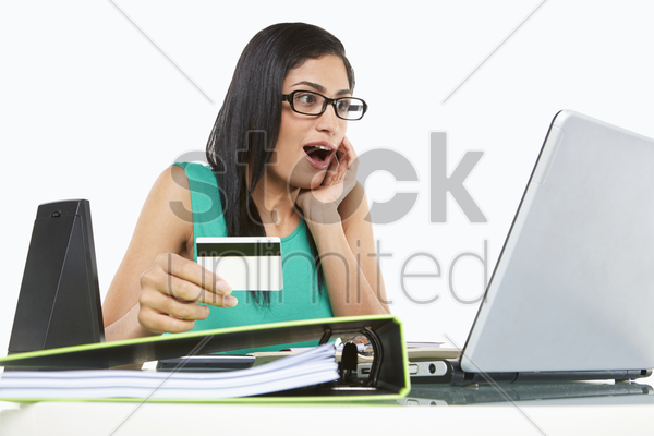 women holding a credit card, looking surprised stock photo