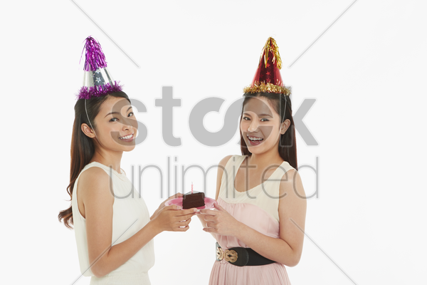 women holding a plate with birthday cake on it stock photo