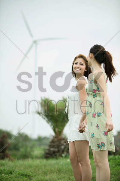 women holding hand outdoors enjoying the cool wind stock photo