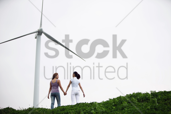 women holding hand outdoors stock photo
