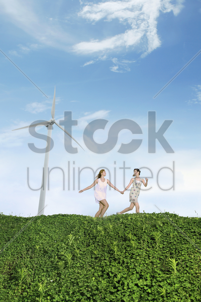 women holding hands and running together stock photo