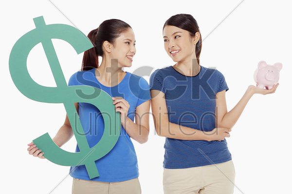women holding up a dollar sign and a piggy bank stock photo