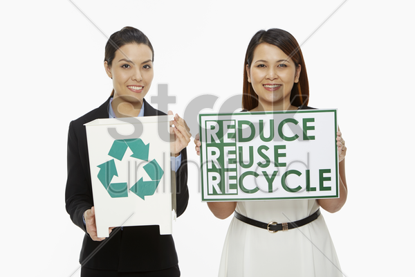 women holding up a recycle bin and a placard stock photo