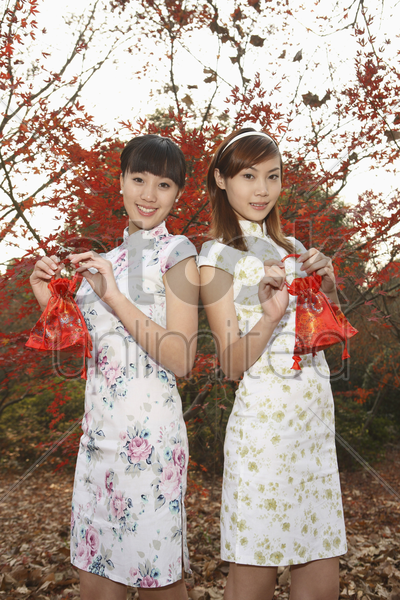 women in cheongsam holding bags stock photo