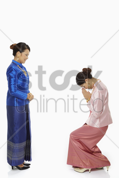 women in traditional clothing greeting one another stock photo