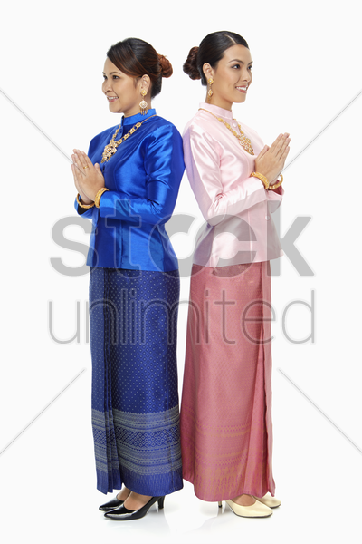 women in traditional clothing showing greeting gesture stock photo