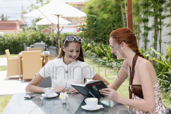 women looking at book and smiling stock photo