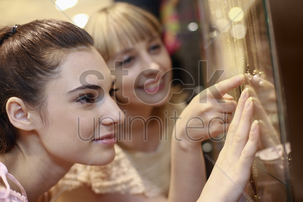 women looking at necklace in display shelf stock photo