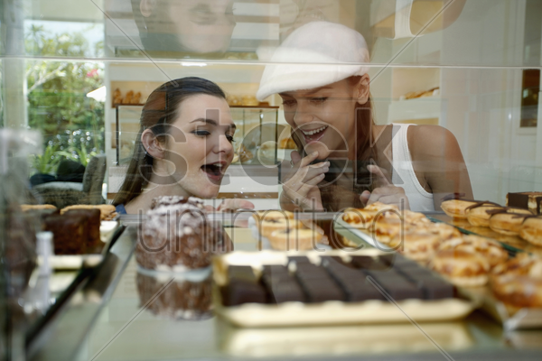 women looking through display case at variety of cakes and tarts stock photo