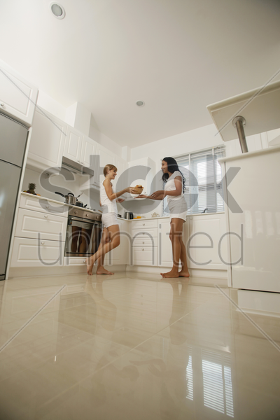 women passing food in the kitchen stock photo