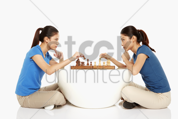 women playing a game of chess stock photo